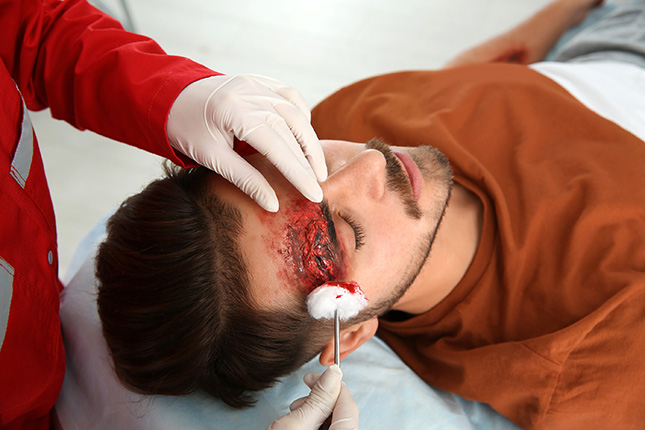 A medical professional cleaning the wound of a auto collision victim