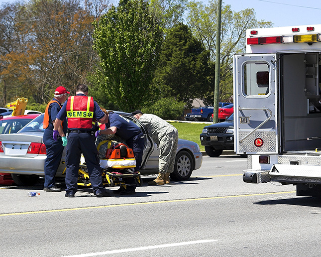 Emergency medical technicians moving a car accident victim from vehicle into the ambulance