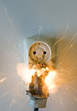 A malfunctioning plug exploding from a wall socket in a flash of electricity.
