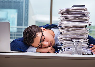 An overworked employee falls asleep on his desk next to a large pile of paperwork