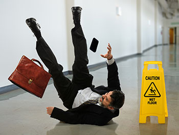 A man slips on a slick floor and falls next to a caution sign.