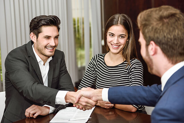 Personal injury lawyer shakes hands with clients